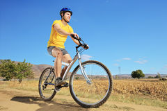 A young male in yellow shirt riding a bike Stock Images