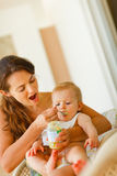 Young mama feeding little baby Royalty Free Stock Image