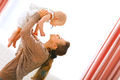 Young mama playing with baby by rising her up. At home royalty free stock photography