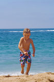 Young man. A young boy running back after getting his feet wet Royalty Free Stock Photography