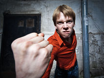 Young man. Wide angle portrait of a young man threatening you with his fist Stock Images