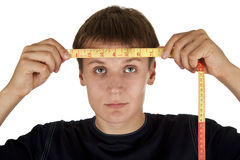 Young man. Measures the line of head, on a white background Stock Photography