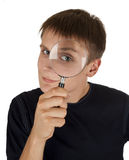 Young man. Look into the camera through a magnifying lens Royalty Free Stock Image
