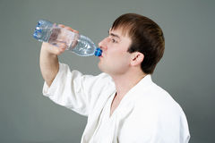 Young man. A young sportsman on karate drinks water Stock Photo