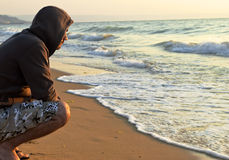 Young man. On the beach looking in the distance Stock Image