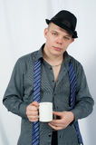 Young man. In a rastegnutoy shirt gets on the hip a mug Stock Image