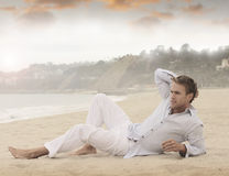 Young man. Young relaxed man laying on beach Stock Images