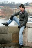 Young Man. A young man sitting outdoor on top of a ancient wall; wearing a winter jacket; a river with a boat and city houses in the backgound Stock Images