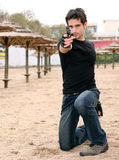 Young Man. A young man at the beach holding a gun Royalty Free Stock Image