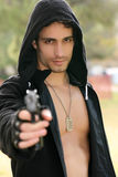 Young Man. An attractive young man holding a gun Stock Photo