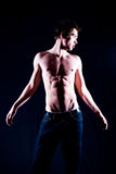 Young man. A young male model on a plain background wearing jeans and no shirt Royalty Free Stock Photos
