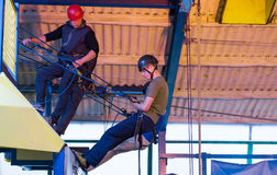 Young Man Abseiling Indoors. Young Man Learning to Abseil with instructors Royalty Free Stock Photo