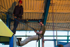 Young Man Abseiling. Young Man Learning to Abseil with instructors Stock Photo