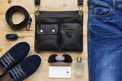 Young man accessories. In casual style, fashion industry, bag, jeans, shoes, belt, eyeglasses, mobile phone, car key and perfume on brushed wood background Stock Image