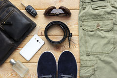 Young man accessories. For spring or summer season in casual style, jeans, shoes, belt, eyeglasses, bag, mobile phone, car key and perfume on brushed wood Stock Image
