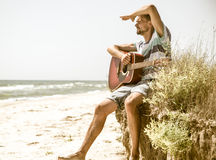 Young man with acoustic guitar on the beach, the concept of leisure and creativity Royalty Free Stock Photography