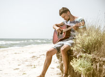 Young man with acoustic guitar on the beach, the concept of leisure and creativity Stock Photography