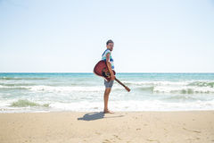 Young man with acoustic guitar on the beach Stock Photography