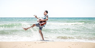 Young man with acoustic guitar on the beach stock image