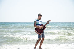 Young man with acoustic guitar on the beach Stock Images