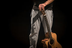Young man with acoustic guitar on black background Royalty Free Stock Photo