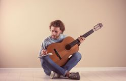Young man with acoustic guitar composing song near wall. Young man with acoustic guitar composing song near grey wall stock images
