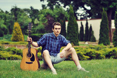 Young man with acoustic guitar in park Stock Photo