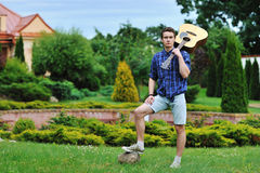 Young man with acoustic guitar in park Stock Image