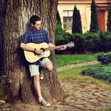 Young man with acoustic guitar in park Stock Images