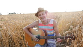 Young man with acoustic guitar at the wheat field. stock footage