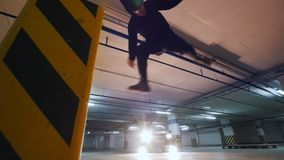 Young man acrobat shows tricks somersault at underground parking. Close up stock footage