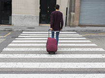 Man across the street with the suitcase. Young man across the street with the suitcase Royalty Free Stock Image