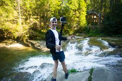 Young man with action camera walk near fast river. In middle of forest royalty free stock photography