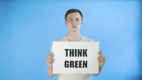 Young man activist with think green poster on blue background. 4K stock video footage