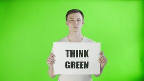 Young man activist with think green poster on chroma key background. 4K stock video