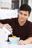 Young Man Adding Sugar To Breakfast Cereal Stock Photos