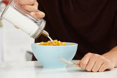 Young Man Adding Sugar To Breakfast Cereal Stock Image