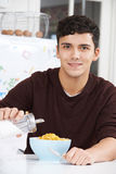Young Man Adding Sugar To Breakfast Cereal Stock Images