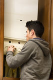 Young man adjusting the boiler or heater Stock Photos
