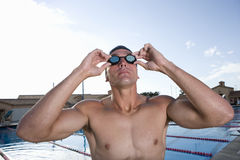 Young man adjusting goggles next to swimming pool. Young men adjusting goggles next to swimming pool Stock Image