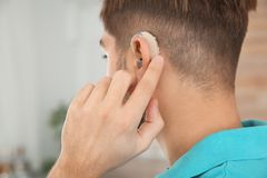 Young man adjusting hearing aid at home royalty free stock images
