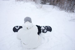 Young man adjusting his snowboard in the snow Royalty Free Stock Image