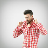 Young man adjusting turned up collar on plaid shirt Royalty Free Stock Photos