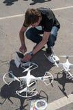 Young man adjusts copter aircraft Royalty Free Stock Photo