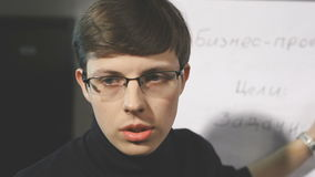 A young man adjusts his glasses and turns to someone. Embarrassed man looks at the camera. The guy with the glasses is afraid. The interview presentation. Timid stock footage