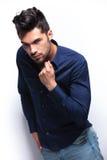 Young man adjusts his shirt Stock Image