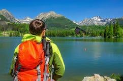 Young man admires high mountains and lake Slovakia Stock Photo