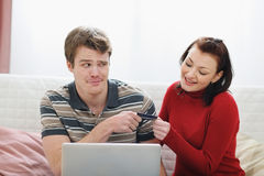 Young man afraid to give credit card to girlfriend Stock Photo