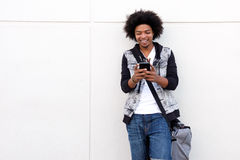 Young man with afro looking at cell phone Stock Photo