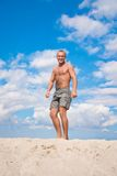 Young man against a blue sky. On a beach Stock Photography